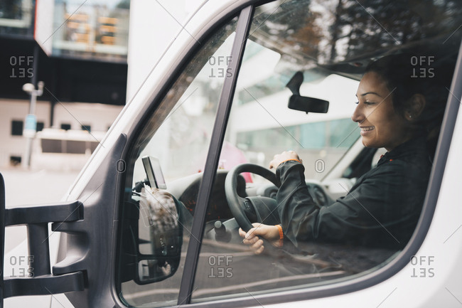 Smiling woman driving delivery van in city