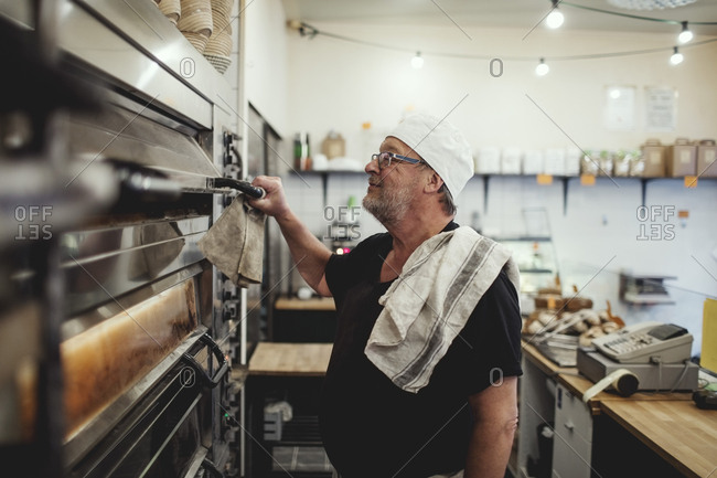 Senior baker standing by oven at bakery