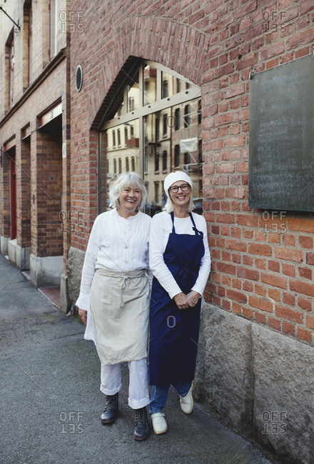 Portrait of smiling female bakers standing by brick wall outside bakery