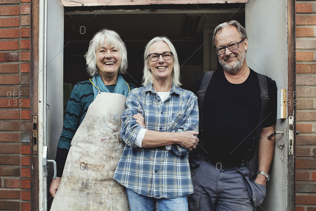 Portrait of smiling senior owners standing at workshop entrance