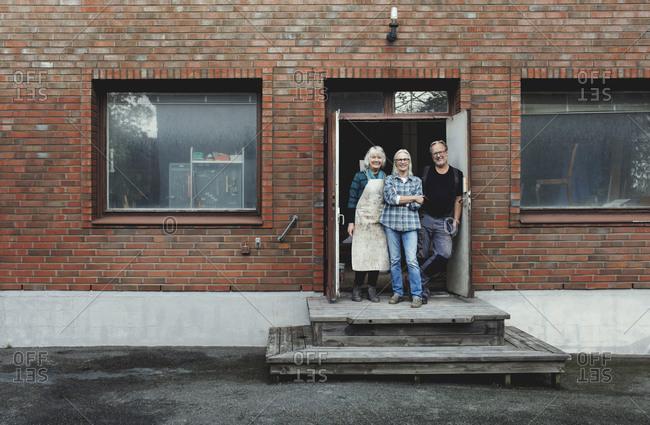 Full length of senior owners standing at workshop entrance