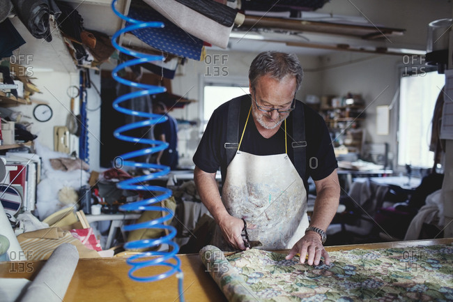 Senior male owner cutting fabric at workbench in workshop