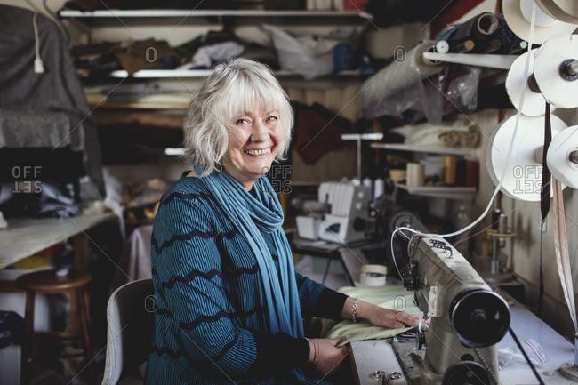 Portrait of smiling senior owner sitting at sewing machine in workshop