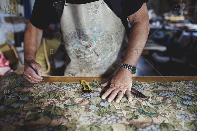 Midsection of owner working on patterned fabric at workbench