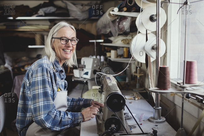 Portrait of smiling owner using sewing machine at workshop