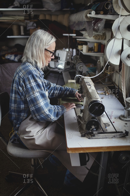 Senior owner using sewing machine at workshop