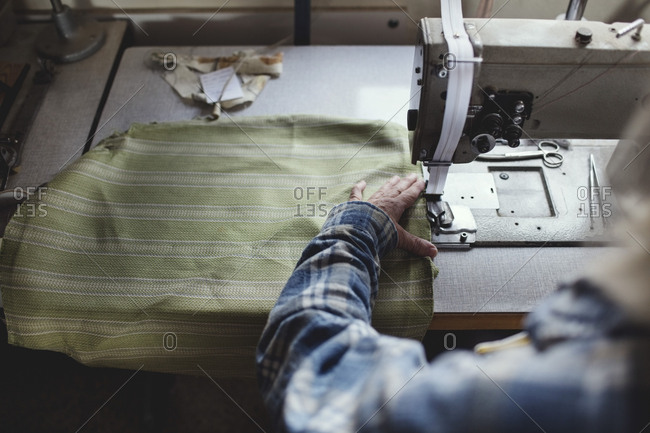 Cropped image of craftsperson sewing green fabric on machine at workshop