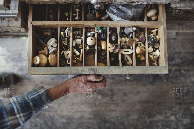 Cropped image of craftsperson opening drawer with knobs at workshop