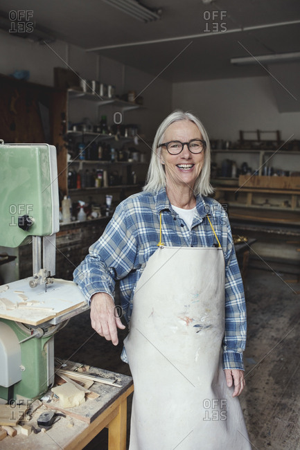 Portrait of smiling senior owner standing by machinery at workshop