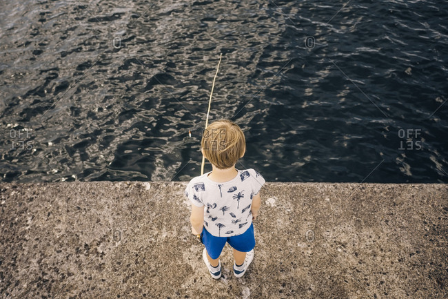 High angle view of boy standing on pier fishing in sea
