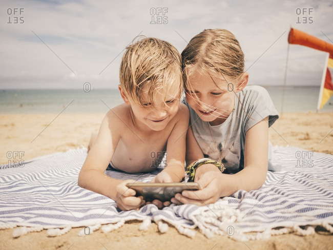 Smiling siblings sharing smart phone while lying on towel at beach against sky