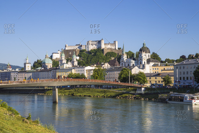 June 19, 2017: Austria, Salzburg, View of Makartsteg bridge over Salzach River and Hohensalzburg Castle above The Old City