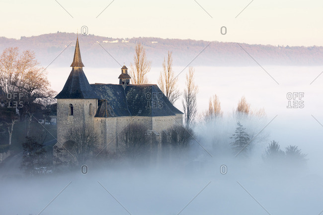 College Notre Dame et St Pantaleon de Turenne in the mist at sunset, Correze; Nouvelle-Aquitaine; France;