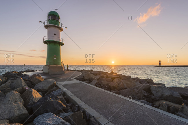 Warnemunde, Rostock district, Baltic coast, Mecklenburg-Western Pomerania, Germany. Pier to the lighthouse at sunrise.