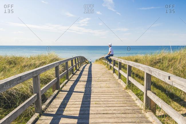 Man standing on a footbridge to Weissenhauser Strand, Ostholstein, Schleswig-Holstein, Germany (MR).