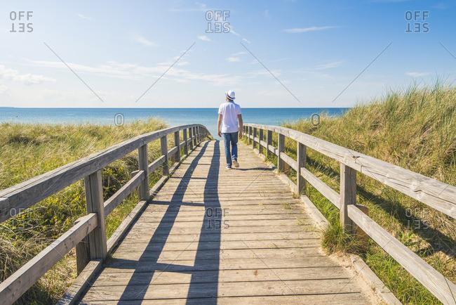 Man walking on a footbridge to Weissenhauser Strand, Ostholstein, Schleswig-Holstein, Germany (MR).
