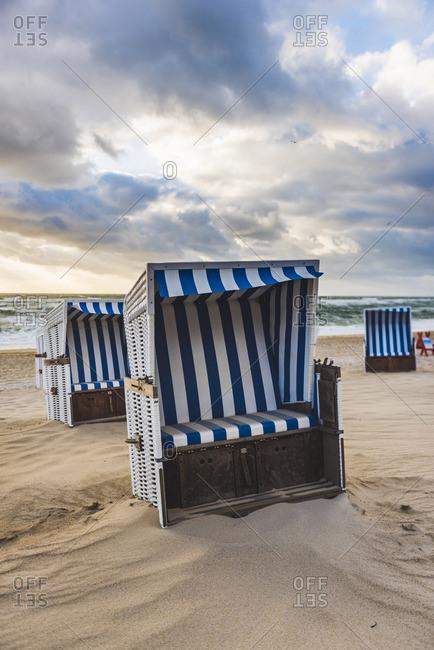 Kampen, Sylt island, North Frisia, Schleswig-Holstein, Germany. Strandkorbs on the beach at sunset.