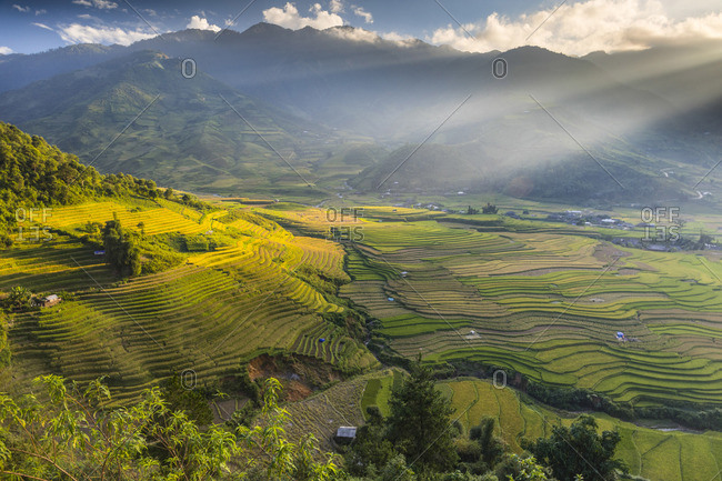 Sun beams over the mountains surrounding the rice terraces at Tu Le, Yen Bai Province, Vietnam, South-East Asia