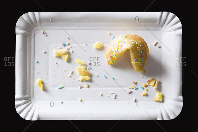 Fortune cookie and leftovers on paper plate