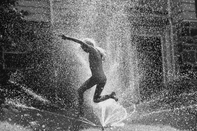 Young girl running though sprinkler in black and white