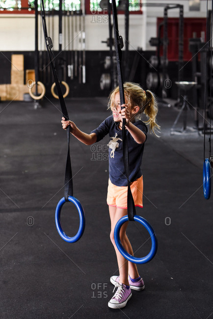 Little girl holding onto steady rings in a gym