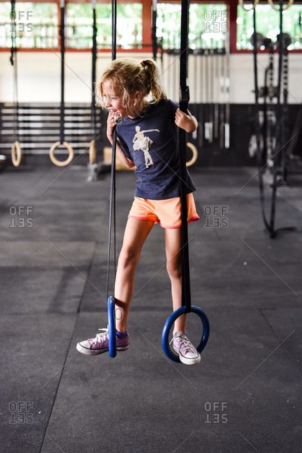 Little girl standing on steady rings in a gym