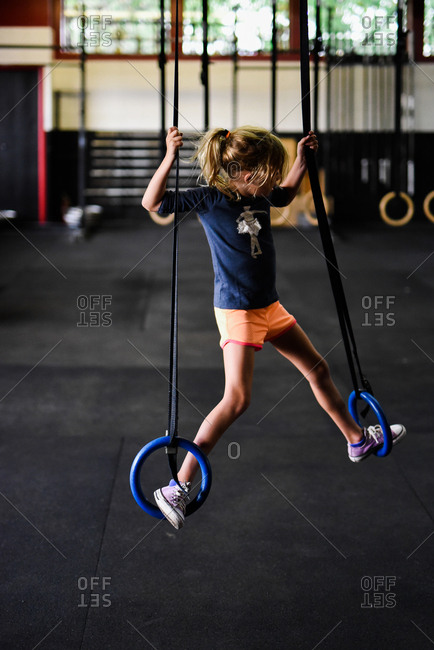 Girl standing on steady rings in a gym