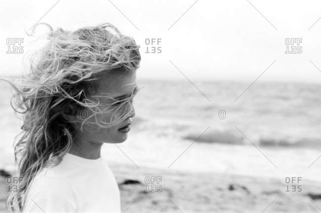 Young girl with wind blown hair on a beach in black and white