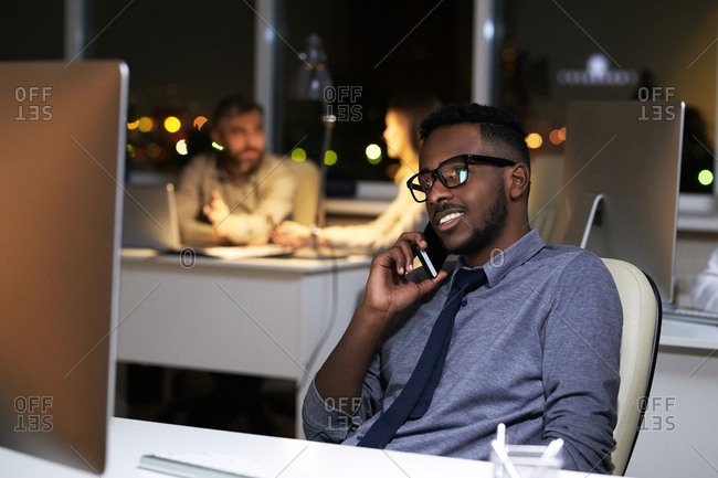 Young man looking at computer and talking on Smartphone in an office at night