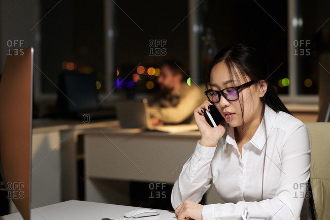 Secretary working overtime talking on phone in an office