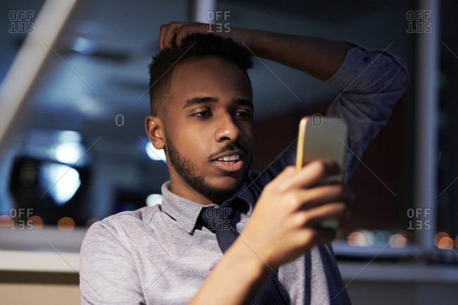 Young handsome black office worker checking Smartphone at the end of working day