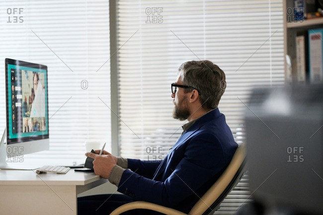 Bearded businessman sitting in his office and having video conference