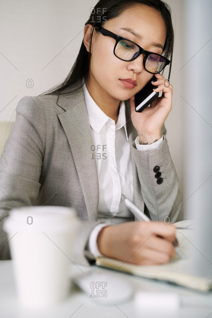 Young Asian female secretary working in office and answering phone calls