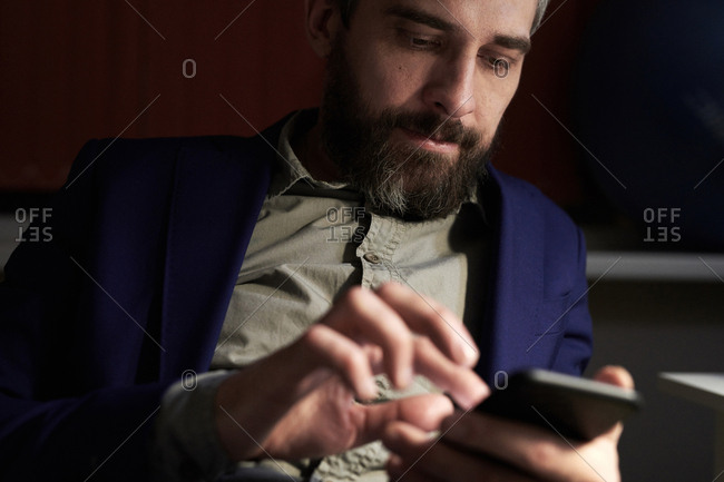 Middle-aged bearded businessman in office in the evening using Smartphone