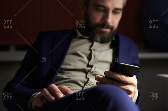Portrait of defocused businessman on his Smartphone in office at night