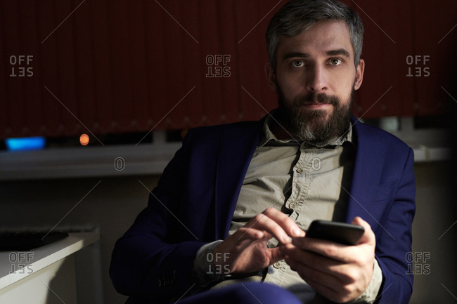 Middle-aged man in dark office holding Smartphone and looking at camera