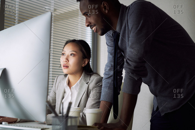 Office worker and his female colleague looking at computer screen