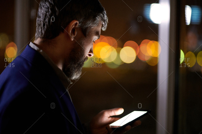 Middle-aged bearded businessman standing by office window in the evening using Smartphone