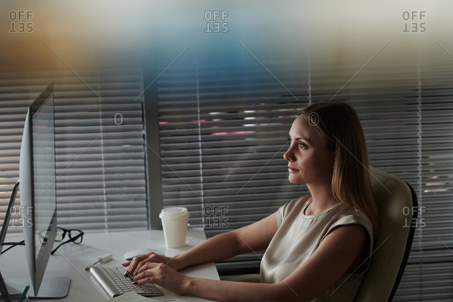 Woman sitting in office typing on computer at night