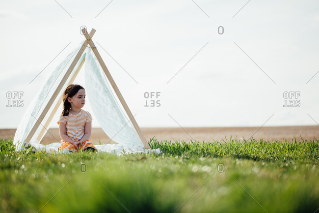 Little girl looking to side in a teepee tent