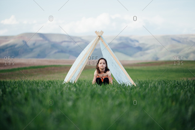 Little girl sitting under a tent