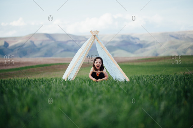 Little girl smiling from under a tent