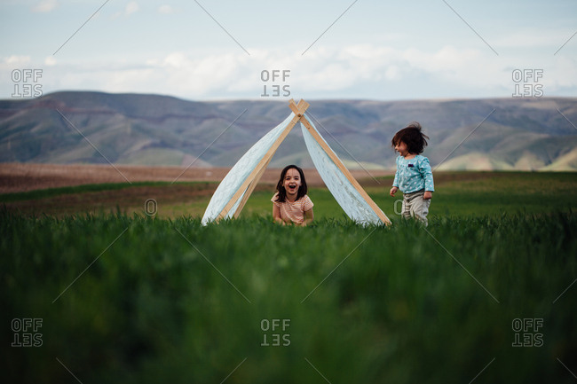 Two girls playing with each other in front of teepee