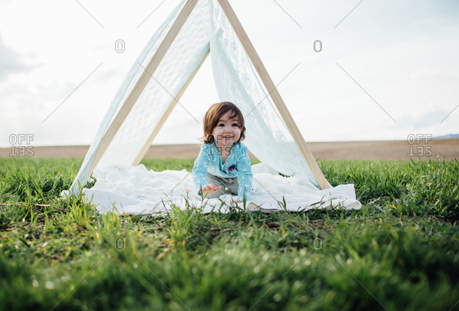 Girl crawling through a tent