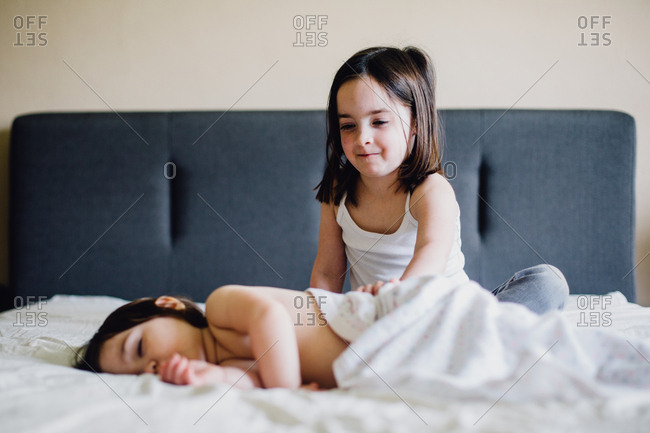 Two sisters on a bed with white sheets, The older sister is trying to wake the younger, she has a smile.