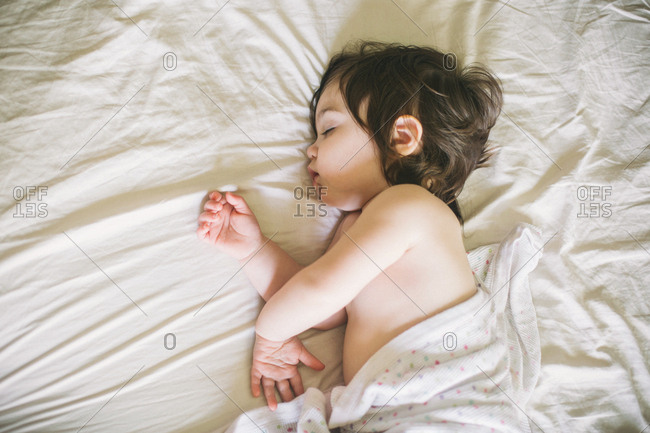 Child sleeping with arms crossed sheet pulled up to tummy.