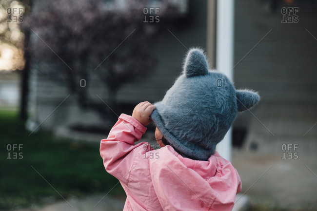 Three year old lifting her hat to the wind, emotional.