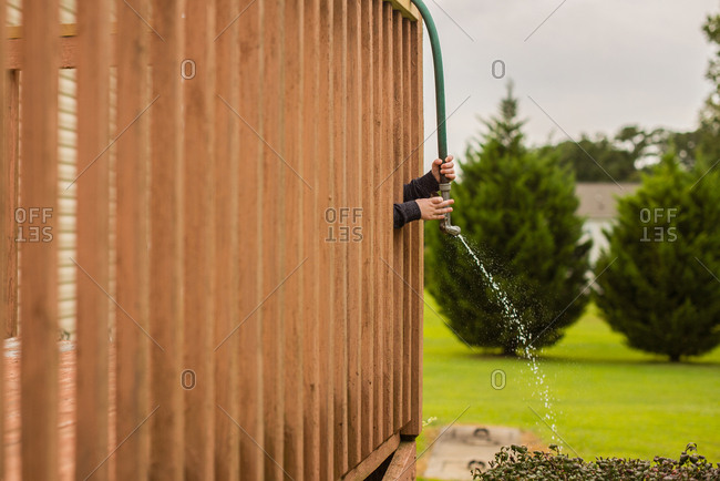 Child watering bush through deck railing