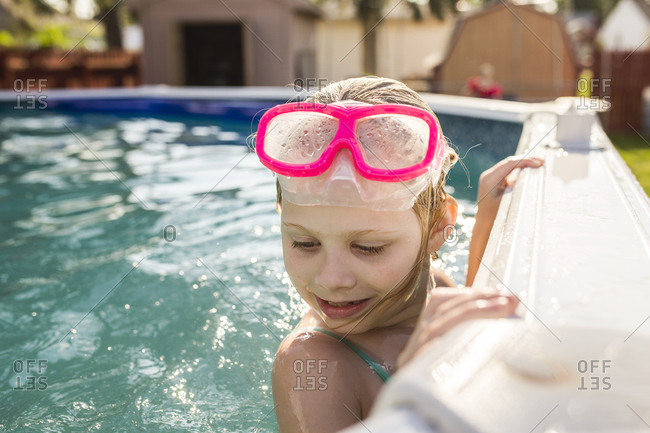 Happy girl with goggles in an above ground swimming pool
