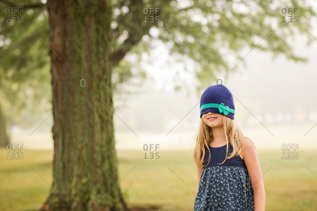 Silly girl with hat pulled over her eyes